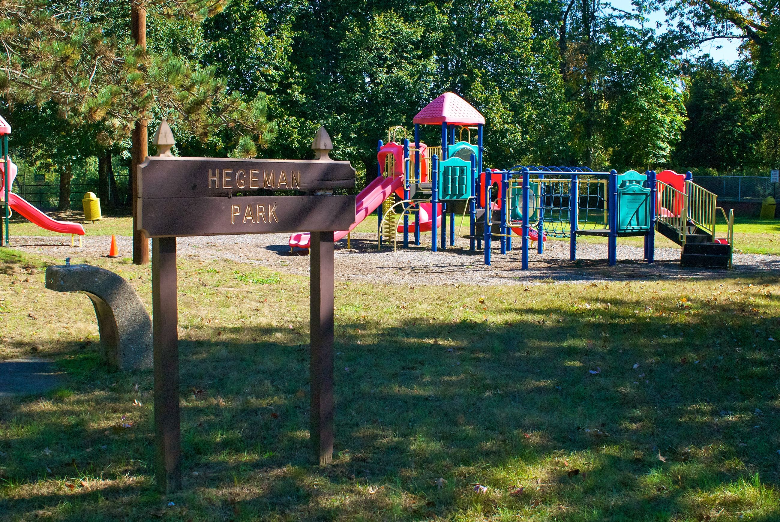 Sign Reading Hegeman Park In Front of a Playground
